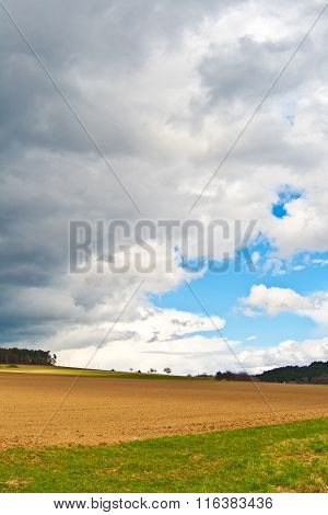 Dark Clouds And Blue Sky Over Fields
