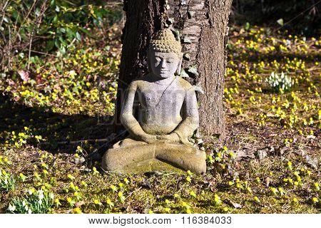 Stone Buddha Meditation In Front Of A Cherry Tree