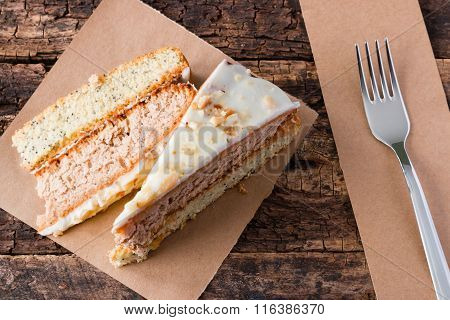 Sliced Homemade Cake On The Paper Next To A Fork On A Wooden Background