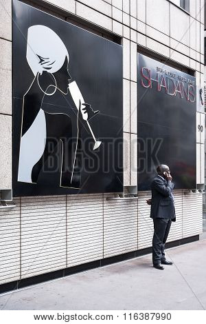 African American Man Speaking On A Mobile Phone While Standing By The Night Club
