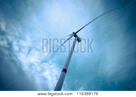 Looking up to wind turbine and blue sky