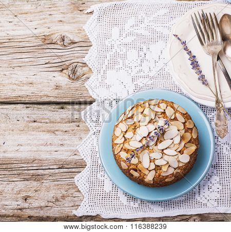 Simple homemade pecan pie decorated with petals of almond  a wooden background