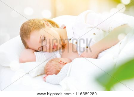 Sleeping Together And Breastfeeding Mother And Newborn Baby In Bed