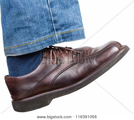 Right Foot In Jeans And Brown Shoe Takes A Step