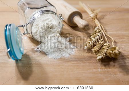 Flour In Glass Jar With Rolling Pin And Sheaves Of Wheat