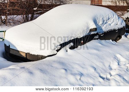 Black Car Under Fresh Snow In Parking Lot