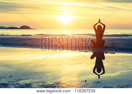 Silhouette of female practicing morning yoga exercises on a beach.