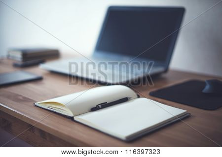 Stylish freelancer workspace with laptop open notepad work tools at home or studio office workplace