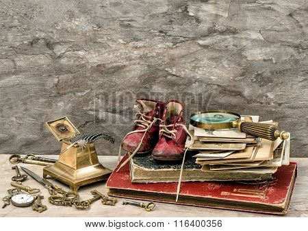 Antique books and photos keys and writing accessories. Nostalgic still life with old baby shoes. Retro style toned picture