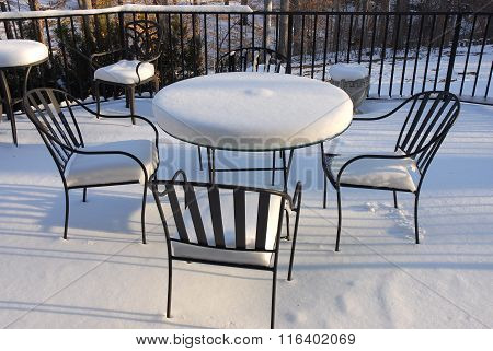 patio furnitures, iron chair and table after snow