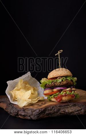 Homemade burger with potato chips on rough woden board, dark background.