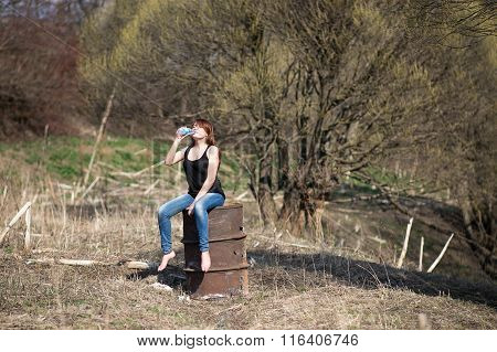 Young country tourist woman sitting in the garden sitting on a rusty barrel and drinking mineral wat