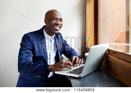 Smiling African Businessman At A Cafe With His Laptop