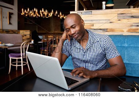 Relaxed African Man At A Cafe Table Using Laptop