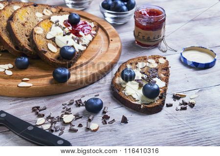 On A Light Wooden Table Sliced Bread With Fruits And Nuts