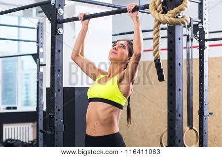 Athlete fit woman performing pull ups in a bar exercising at gym.