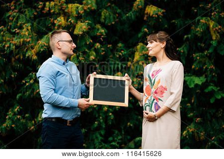 Expecting Pregnant Happy Stylish Couple Holding A Blank Charcoal Board.