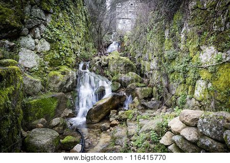a stream through stones with moss in Castelo Novo, Portugal