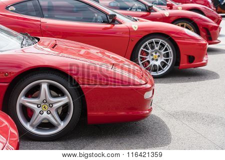 Row of red Ferrari on public display in a car show