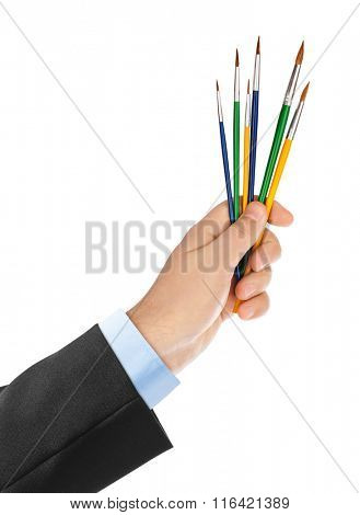 Hand with multicolored paintbrushes isolated on white background