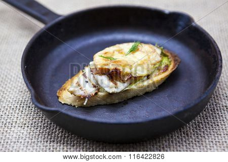 Home baked hot sandwich with chicken cheese, onion, chile pepper, garlic  on a cast-iron pan on a textiles background