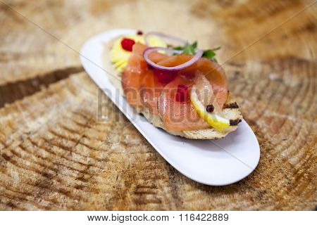 Fresh Spanish tapas on bread baguette smoked Norwegian salmon with black olive butter, herbs and onions. An excellent wood background for the menus, the restaurant, the Cafe Mediterranean cuisine