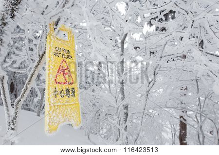 warning caution sign board on snowy trees on hill