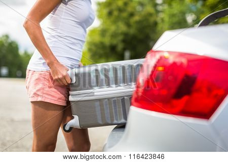 Young woman putting a have suitcase into her car's trunk