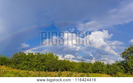 Summer Landscape With Double Rainbow, Green Grass And Clouds