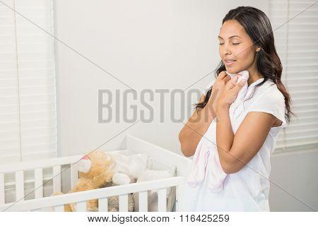 Smiling brunette holding onesie in bedroom