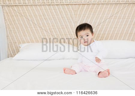 Cute baby on bed looking at the camera