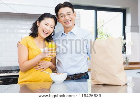 Portrait of happy expectant couple in the kitchen in morning