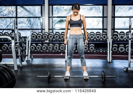 Fit woman preparing herself for barebell exercise at gym