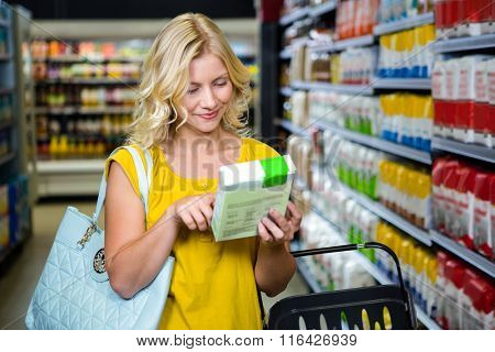 Smiling pretty blonde woman reading a box in supermarket