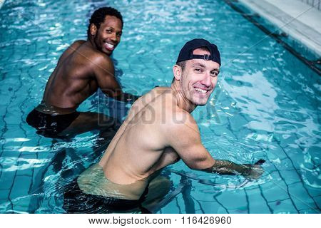 Fit smiling men doing swimming bike in swimming pool