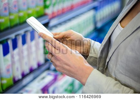 Woman using her smartphone in aisle in supermarket