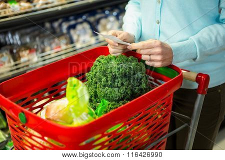 Mid section of a woman with grocery list in supermarket