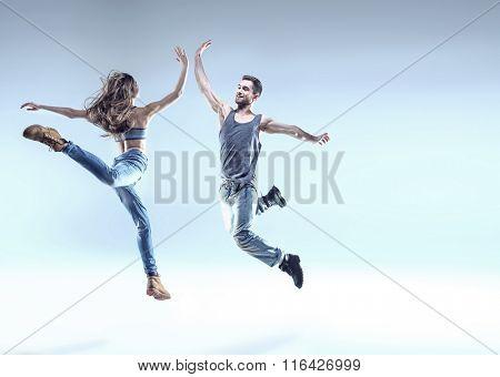 young handsome couple dancing hip-hop, studio background