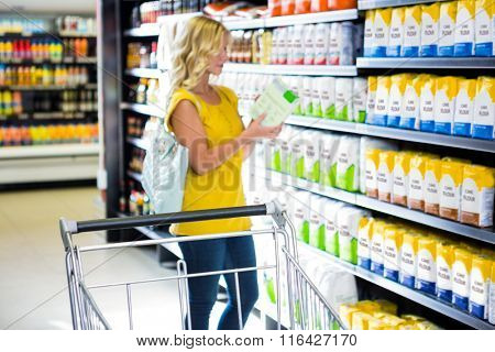 Woman taking a product in aisle in supermarket