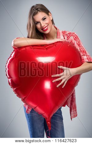 young woman in a bright red dress, holding a giant inflatable Valentines Day heart