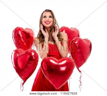 Adorable girl surrounded by red hearts looking up