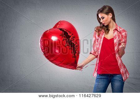 Beautiful woman looking at big heart shaped balloon