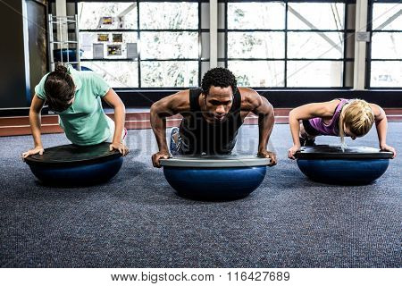 Fit people doing bosu push ups in crossfit