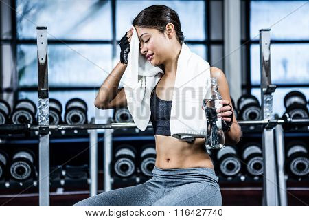 Muscular woman sitting on bench while holding bottle of water and a towel in crossfit
