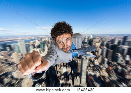 Businessman superhero flying over a city