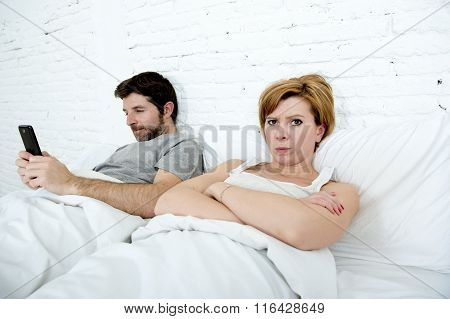 Young Couple In Bed Unsatisfied Wife Bored Frustrated And Angry While Internet Addict Husband Is Usi