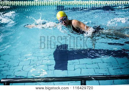 Side view of swimmer woman swimming in the swimming pool