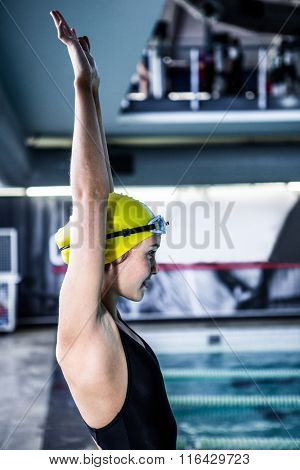 Side view of a woman swimmer ready to dive in the swimming pool