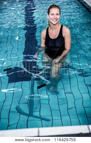 Portrait of a smiling woman cycling in the swimming pool