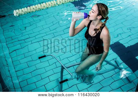 Fit woman cycling while drinking water in swimming pool